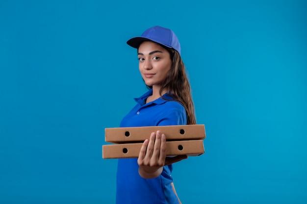 Giovane ragazza delle consegne in uniforme blu e cappuccio che tiene le scatole per pizza guardando la fotocamera sorridente fiducioso in piedi felice e positivo su sfondo blu Foto Gratuite