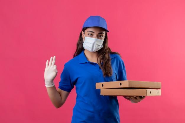 Giovane ragazza delle consegne in uniforme blu e cappuccio che indossa la maschera protettiva per il viso e guanti tenendo le scatole per pizza guardando la telecamera con fiduciosa espressione seria facendo segno ok in piedi su rosa b Foto Gratuite