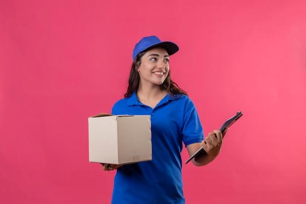青い制服を着た若い配達の少女とキャップパッケージボックスパッケージとピンクの背景の上に元気に立っている笑顔をよそ見クリップボードを保持 無料写真