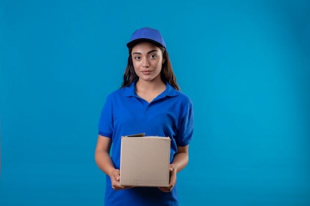 青い背景に自信を持って幸せと肯定的な立っている笑顔カメラを見て青い制服とキャップ保持ボックスパッケージの若い配達の少女 無料写真