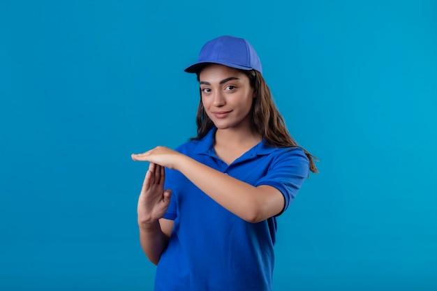 Молодая доставщица в синей форме и кепке выглядит уверенно, делая жест тайм-аута с руками, стоящими на синем фоне Бесплатные Фотографии