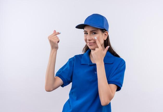 Молодая доставщица в синей униформе и кепке трет пальцы, указывая пальцем в глаза, ожидая оплаты Бесплатные Фотографии