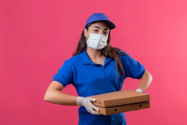 Молодая доставщица в синей форме и кепке, в защитной маске и перчатках, держит коробки с пиццей и смотрит в камеру с серьезным уверенным выражением лица, стоя на розовом фоне Бесплатные Фотографии