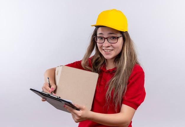 恥ずかしがり屋の笑顔でカメラを見て赤いポロシャツと黄色の帽子保持ボックスパッケージとクリップボードの若い配達の女の子 無料写真