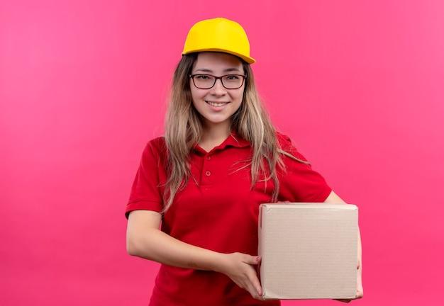 自信を持って笑顔のカメラを見て赤いポロシャツと黄色の帽子保持ボックスパッケージの若い配達の女の子 無料写真