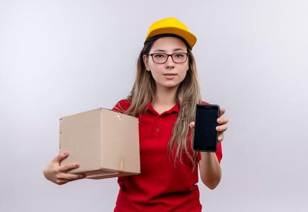 赤いポロシャツと黄色い帽子の箱のパッケージを保持している若い配達の女の子は、顔に真剣な自信を持ってカメラを見ているスマートフォンを示しています 無料写真
