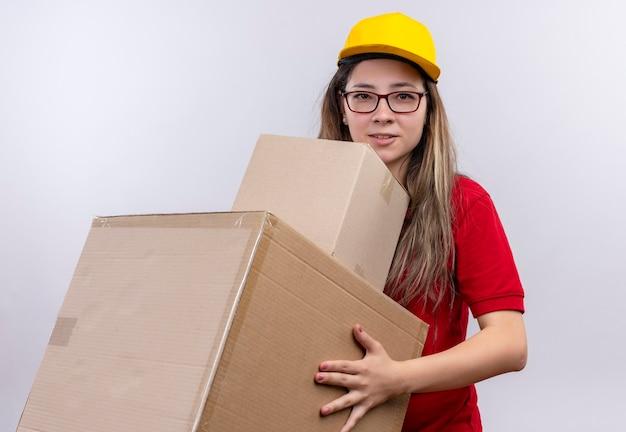 顔に自信を持って笑顔でカメラを見て段ボール箱を保持している赤いポロシャツと黄色の帽子の若い配達の女の子 無料写真