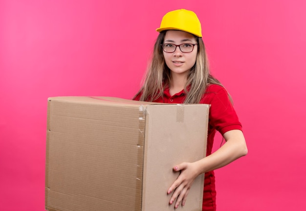 カメラの笑顔を見て大きな段ボール箱を保持している赤いポロシャツと黄色の帽子の若い配達の女の子 無料写真
