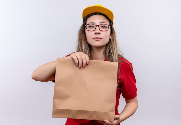 真剣な自信を持ってカメラを見ている赤いポロシャツと黄色の帽子の紙のパッケージを保持している若い配達の女の子 無料写真