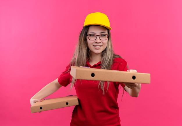赤いポロシャツと黄色い帽子の若い配達の女の子は、カメラの笑顔に伸びるピザの箱を保持しています 無料写真