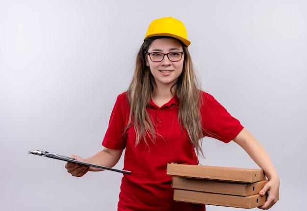 自信を持って笑顔でカメラを見てピザボックスとクリップボードのスタックを保持している赤いポロシャツと黄色の帽子の若い配達の女の子 無料写真