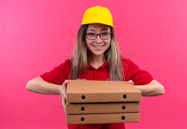 広く笑っているカメラを見ているピザの箱のスタックを保持している赤いポロシャツと黄色の帽子の若い配達の女の子 無料写真