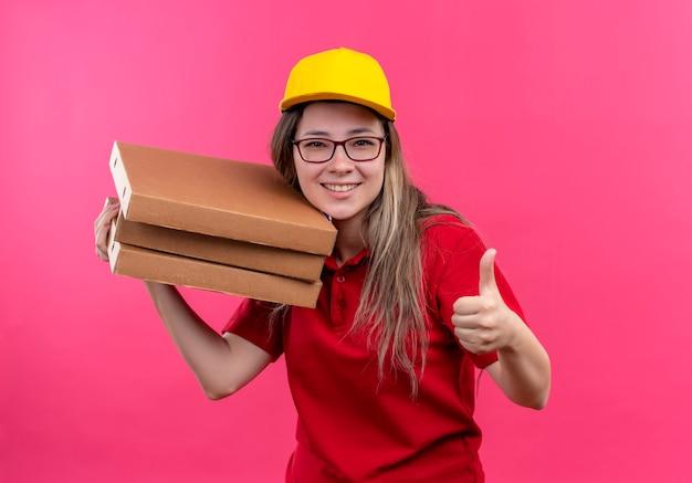 赤いポロシャツと黄色い帽子の若い配達の女の子は、親指を上手に見せて元気に笑っているカメラを見てピザボックスのスタックを保持しています 無料写真