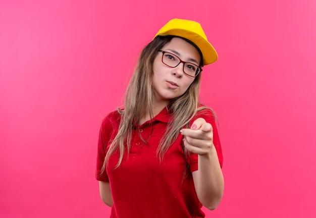 カメラに人差し指で指している赤いポロシャツと黄色のキャップの若い配達の女の子 無料写真
