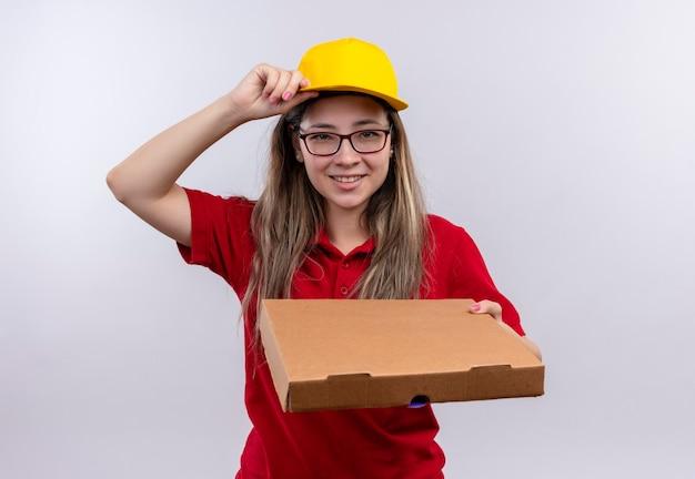 Giovane ragazza delle consegne in maglietta polo rossa e cappuccio giallo che tiene la scatola della pizza guardando sorridente fiducioso toccando il suo cappuccio Foto Gratuite