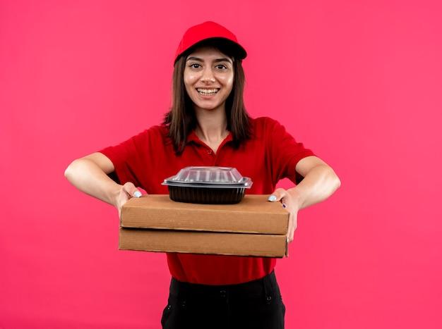 Молодая доставщица в красной рубашке поло и кепке держит коробки для пиццы и продуктовый пакет, глядя в камеру, улыбаясь со счастливым лицом, стоящим на розовом фоне Бесплатные Фотографии