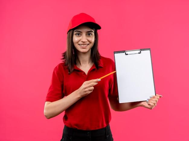Giovane ragazza di consegna che indossa la maglietta polo rossa e cappuccio che tiene appunti con pagine vuote puntando con una matita a sorridere con la faccia felice in piedi su sfondo rosa Foto Gratuite
