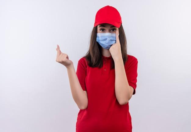 Молодая доставщица в красной футболке в красной кепке носит маску для лица и просит совета на изолированном белом фоне Бесплатные Фотографии