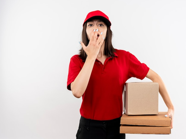 赤い制服とキャップ保持ボックスパッケージと白い背景の上に立っている手で口を覆ってショックを受けているカメラを見てピザボックスを身に着けている若い配達の女の子 無料写真