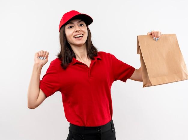 Молодая доставщица в красной форме и кепке держит бумажный пакет, сжимая кулак, счастливая и взволнованная, стоя на белом фоне Бесплатные Фотографии