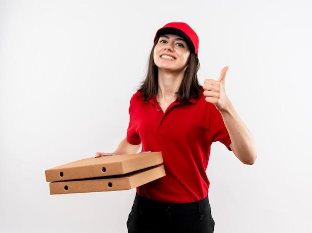 Giovane ragazza di consegna che indossa l'uniforme rossa e cappuccio che tiene le scatole per pizza guardando la fotocamera sorridente con la faccia felice che mostra i pollici in su in piedi su sfondo bianco Foto Gratuite
