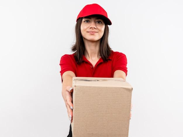 Giovane ragazza di consegna che indossa l'uniforme rossa e cappuccio che allunga fuori il pacchetto della scatola che sorride amichevole che si leva in piedi sopra la parete bianca Foto Gratuite