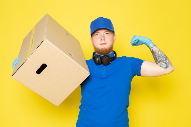 Young delivery man in blue polo blue cap white jeans backpack holding a box on yellow Free Photo