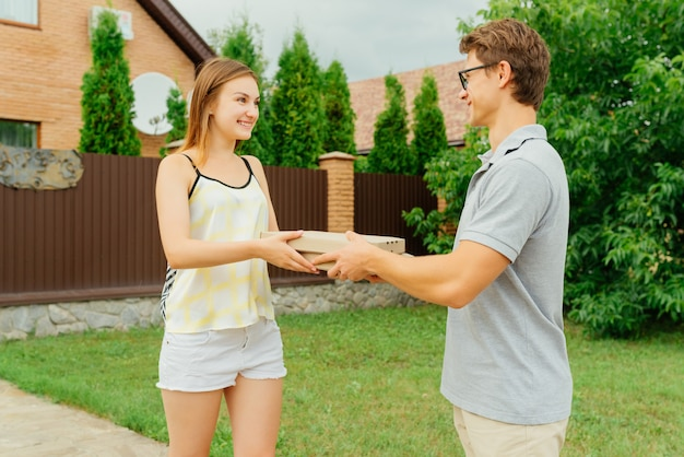 Premium Photo | Young delivery man giving two boxes with pizza to  attractive woman, near the private house, outdoors.