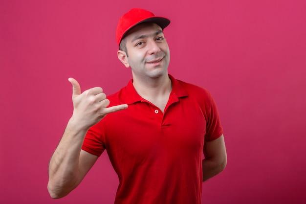 赤いポロシャツとキャップを作る若い配達人は私に分離のピンクの背景に元気に笑みを浮かべて自信を持って探しているジェスチャーを呼び出す 無料写真