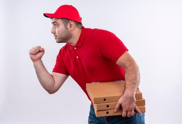 赤い制服を着た若い配達人と白い壁に真面目な顔で横に立っている拳を握り締めるピザの箱を保持しているキャップ 無料写真
