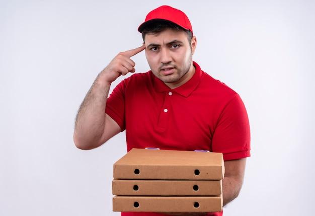 赤い制服を着た若い配達人と、白い壁の上に立っているタスクに焦点を当てて自信を持って見える彼の寺院を指で指しているピザの箱を持っている 無料写真