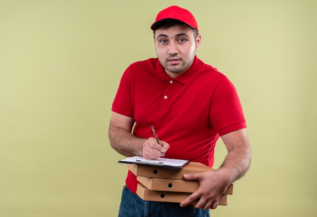 赤い制服を着た若い配達人と緑の壁の上に立ってフレンドリーな笑顔の空白のページにピザの箱を保持しているキャップ 無料写真