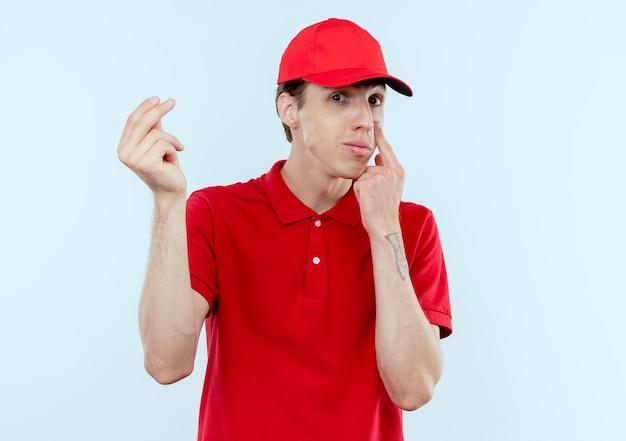 白い壁の上に立って支払いを待っている彼の目に指で指してお金を求めて指をこすりながら正面を見て赤い制服と帽子の若い配達人 無料写真