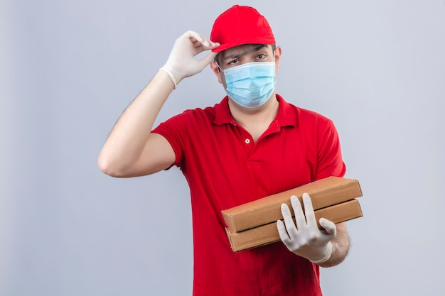 Young delivery man in red polo shirt and cap in medical mask holding pizza boxes making greeting gesture touching his cam with hand with serious face skeptic and displease Free Photo
