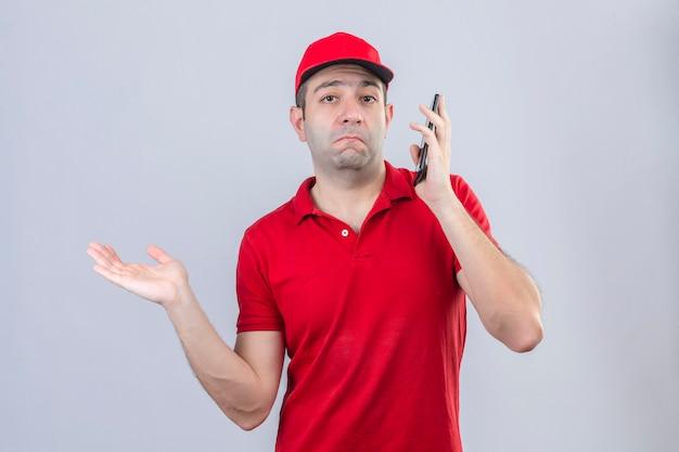 Giovane uomo di consegna in maglietta polo rossa e cappuccio parlando al telefono cellulare espressione confusa e all'oscuro con il braccio alzato avendo dubbi su sfondo bianco isolato Foto Gratuite