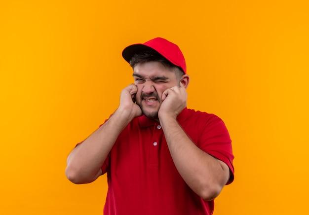 Giovane fattorino in uniforme rossa e berretto che chiude epoche con le dita con espressione infastidita per il rumore Foto Gratuite