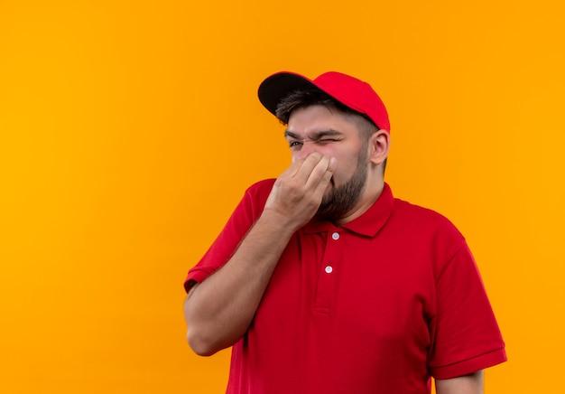 Giovane fattorino in uniforme rossa e cappuccio che chiude il naso con le dita che soffrono di puzza Foto Gratuite