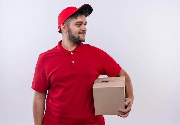 Giovane fattorino in uniforme rossa e pacchetto della scatola della tenuta del cappuccio che osserva da parte sorridente fiducioso Foto Gratuite