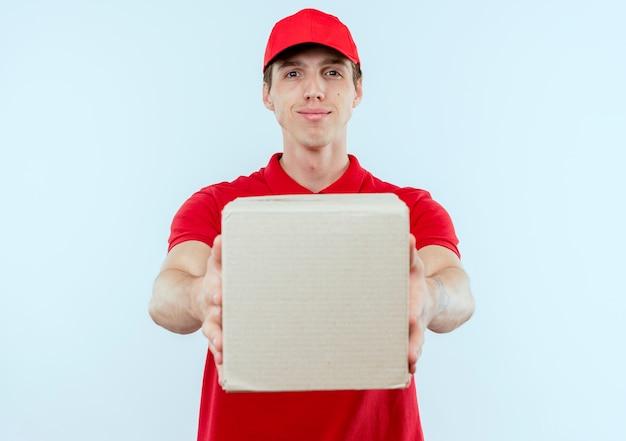 Giovane fattorino in uniforme rossa e cappuccio che tiene la scatola di cartone guardando in avanti con espressione fiduciosa in piedi sopra il muro bianco Foto Gratuite