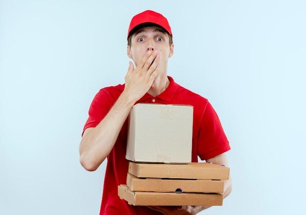 Giovane fattorino in uniforme rossa e cappuccio che tiene le scatole della pizza e il pacchetto della scatola che sembra sorpreso e stupito in piedi sopra il muro bianco Foto Gratuite