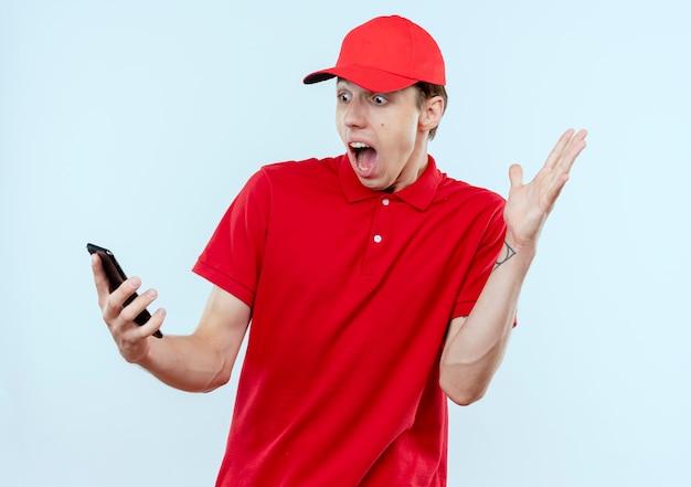 Giovane fattorino in uniforme rossa e cappuccio che tiene smartphone guardando sorpreso e confuso con il braccio alzato in piedi sopra il muro bianco Foto Gratuite