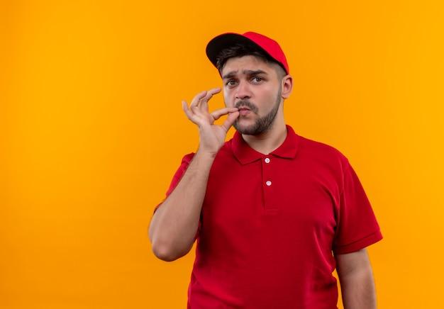Giovane fattorino in uniforme rossa e berretto che fa gesto di silenzio come chiudere la bocca con una cerniera Foto Gratuite