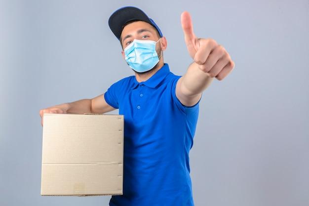 Молодой курьер в синей рубашке поло и кепке в медицинской защитной маске, стоящий с картонной коробкой, показывая большой палец на камеру на изолированном белом фоне Бесплатные Фотографии