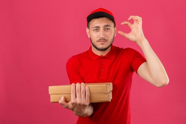 Молодой курьер в красной рубашке поло и кепке стоит с коробками для пиццы, глядя в камеру, показывая знак размера пальцами на изолированном розовом фоне Бесплатные Фотографии