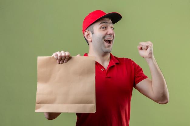격리 된 녹색 배경 위에 행복한 얼굴로 승리를 축하하는 주먹을 올리는 종이 패키지를 들고 빨간색 유니폼을 입고 젊은 배달 남자 무료 사진