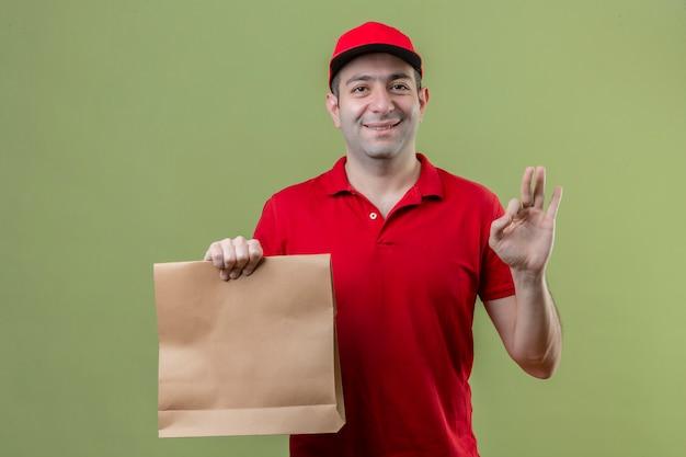 고립 된 녹색 배경 위에 확인 서명 하 고 친절 하 고 웃 고 종이 패키지를 들고 빨간 유니폼을 입고 젊은 배달 남자 무료 사진