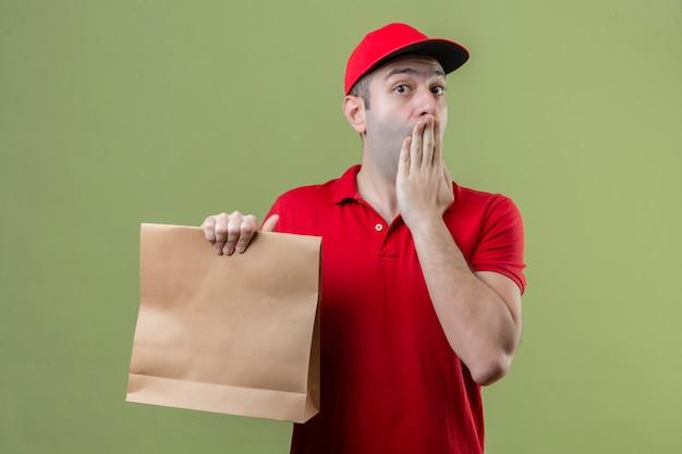 종이를 들고 빨간색 유니폼을 입고 젊은 배달 남자는 고립 된 녹색 배경 위에 손으로 입을 덮고 충격 무료 사진