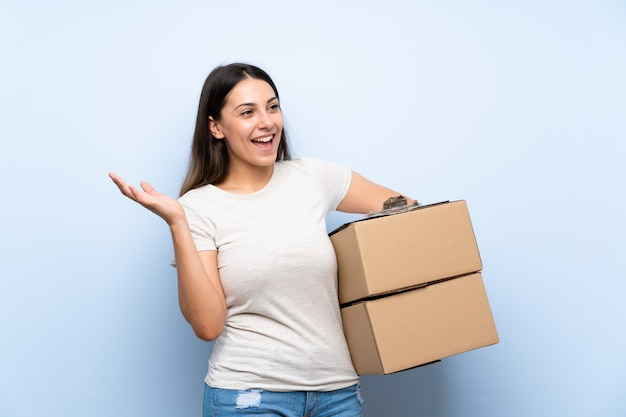 Young delivery woman over blue brick wall with surprise facial expression Premium Photo