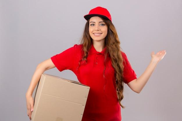 赤いポロシャツと段ボール箱に立っているキャップを着ている若い配達の女性は元気に笑みを浮かべて提示し、孤立した白い背景の上にカメラを見て手のひらで指して 無料写真