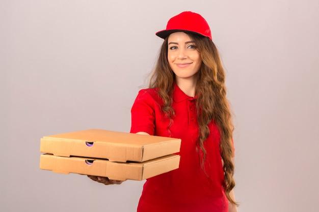 赤いポロシャツと孤立した白い背景にフレンドリーな笑顔の顧客にそれらを与えるピザの箱で立っているキャップを着ている若い配達の女性 無料写真